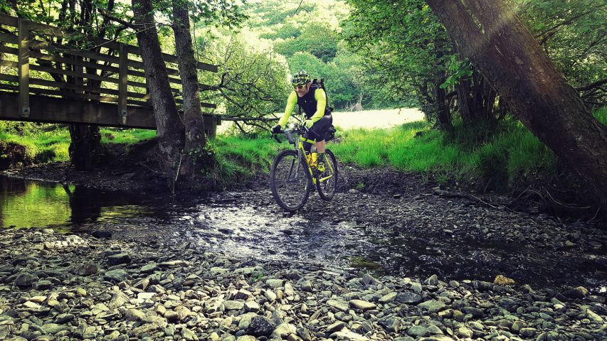 Cyclist riding a Kinesis Tripster AT through a stream
