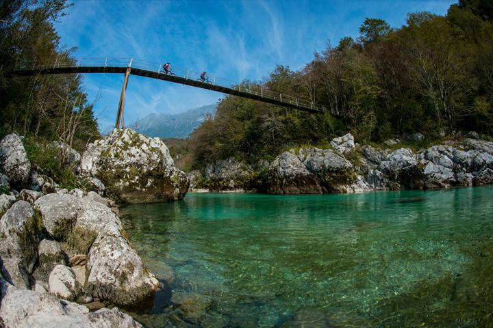 Two riders ona bridge over turquoise waters