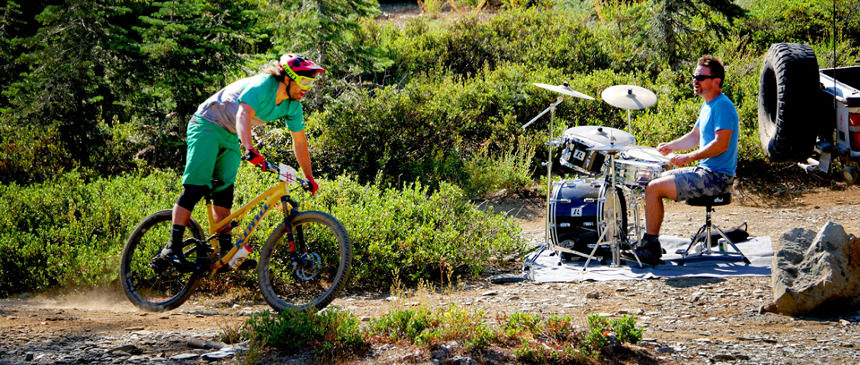 Rider flying past a drummer at Downieville classic