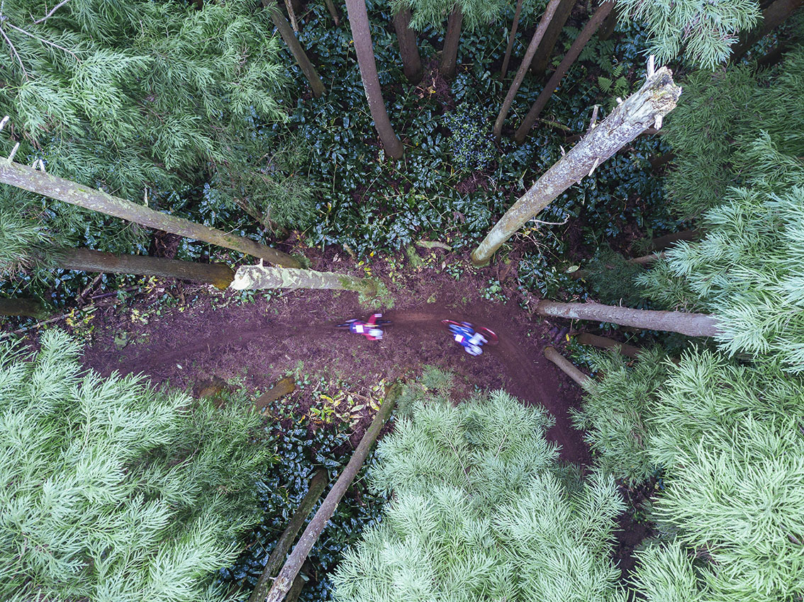 Shot from the treetops looking down on two riders on a snaking trail