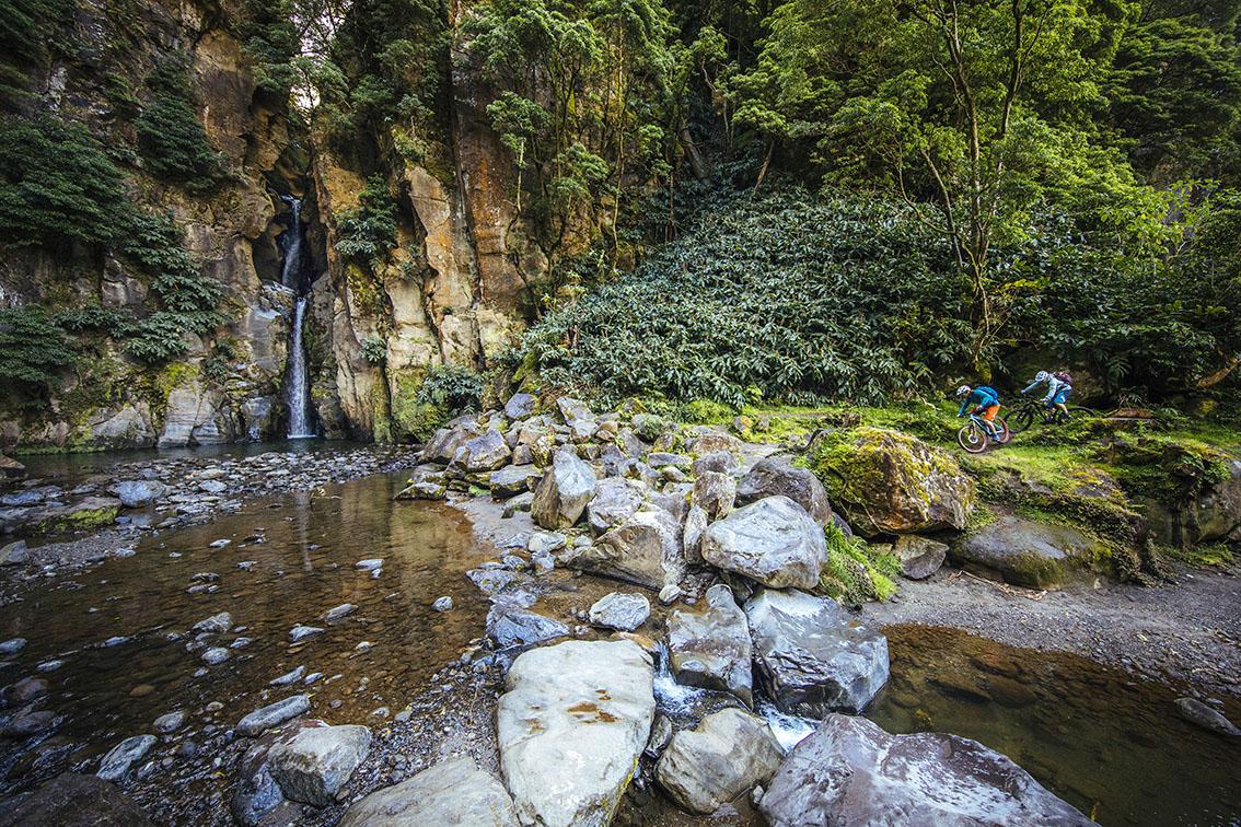 Two mountain bikers approaching a creek with a waterfall