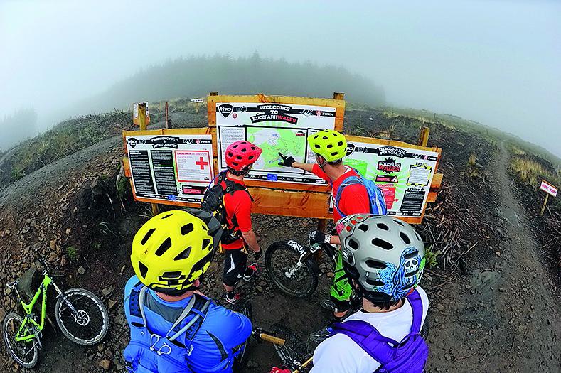 Riders looking at trailhead signage